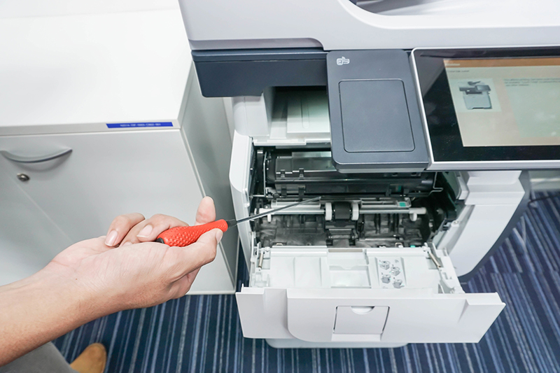 man with screwdriver in hand fix printer